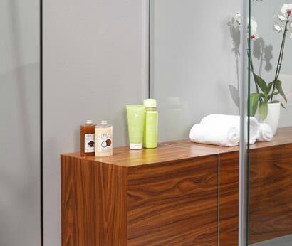 Eine unserer Spezialitäten: Glasausschnitte ermöglichen Ihnen einen individuellen Spielraum bei der Gestaltung Ihrer Dusche – beispielsweise eine wasserdichte Sitzecke mit bedrucktem Holzdekor