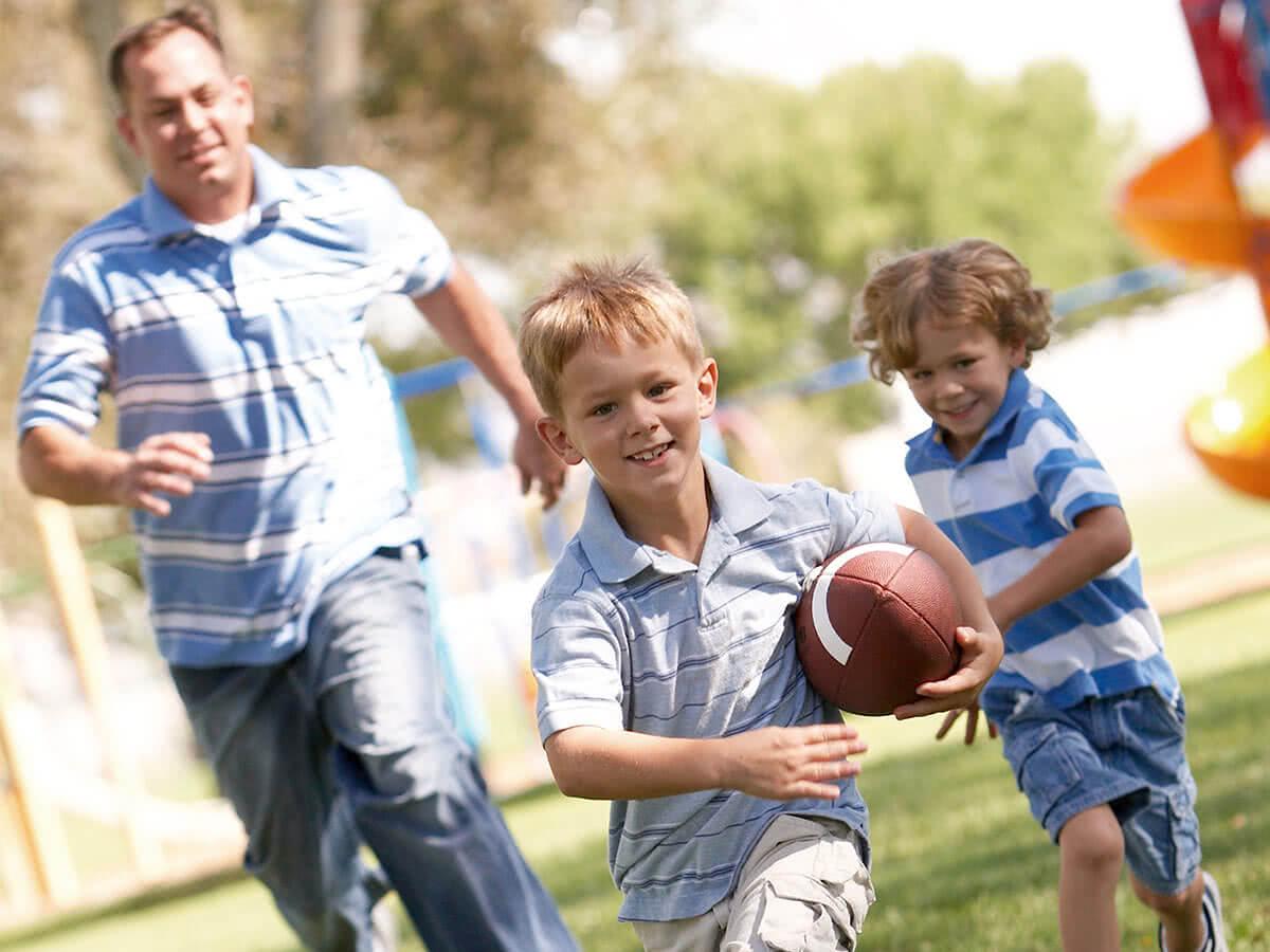 Familie mit ballspielenden Kinden