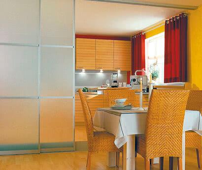 Essbereich und Küche werden durch die Motion 400 sanft getrennt, der mattweiße Siebdruck und die Sprossentäfelung bewahren das mediterrane Flair.