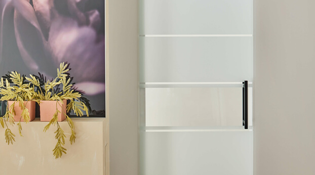 Glastür passend zum Motiv auf der Glasdusche: Die Schiebetür Motion 1300 mit schwarzen Beschlägen ist hier passend zum Motiv der Duschtür gestaltet.